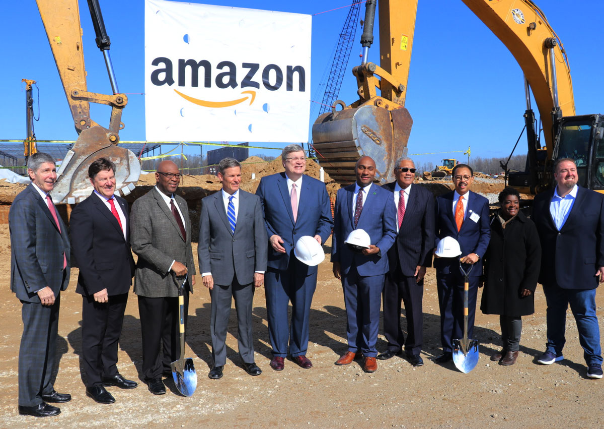 Group of people standing in front of construction equipment